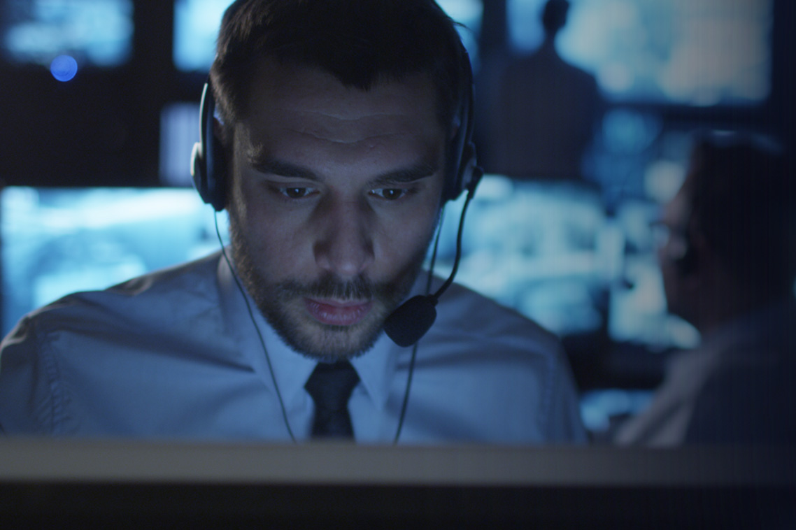 Security representative with headset on a computer